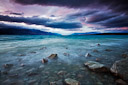 Evening colors appear in the sky over glacial blue Lake Pukaki. South Island, New Zealand.