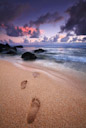 Footprints lead to the surf. Kauai, Hawaii.