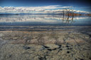 A muddy shoreline gives way to a serene view of the Salton Sea, California.